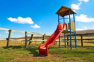 speeltuin op het platteland met een rode glijbaan en landelijke achtergrond foto