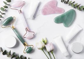 cosmetische productcrèmebuizen, gezichtsroller en eucalyptus op een marmeren achtergrond foto