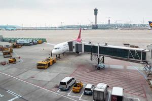 Seoel, Zuid-Korea 2016 - Luchthavenfunctionarissen dragen de lading voor het vliegtuig op de internationale luchthaven Incheon in Zuid-Korea foto