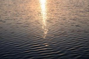 zonneschijn gloeit op golvend water in het meer foto