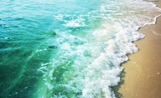 zomer achtergrond van turquoise kleur zee met golf op het zandstrand foto