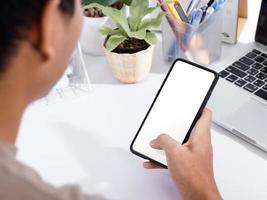 man met een smartphone leeg scherm mock-up op het witte bureau white foto