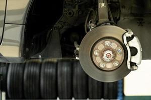 schijfauto close-up - monteur die auto-onderdelen losschroeft terwijl hij werkt onder een opgeheven auto - autoserviceconcept foto