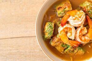 zure soep gemaakt van tamarindepasta met garnalen en groenteomelet - Aziatisch eten foto