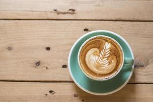 hete cappuccino met latte art op houten achtergrond foto