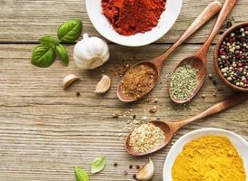 een selectie van verschillende kleurrijke kruiden op een houten tafel in kommen en lepels foto