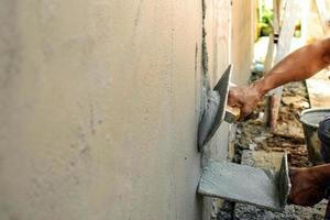 huisverbetering en verbeteringsconcept close-up van arbeiders die muren pleisteren om huizen te bouwen foto