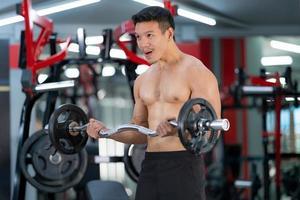 sportieve man traint met een zware barbell in de sportschool foto