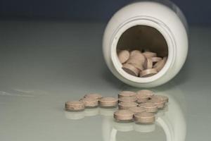 pillen zijn verspreid over de tafel behandeling of zelfmoord foto