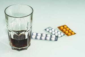 pillen zijn verspreid over de tafel whisky- of rumbehandeling of zelfmoord foto