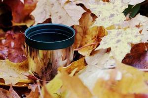 groene thermos roestvrijstalen beker in herfstbladeren foto