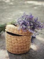 behang paarse bloemen op een rieten mand foto