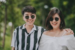gelukkig aziatisch lgbt-lesbisch paar dat verliefd is en zich amuseert en knuffelt in het park foto