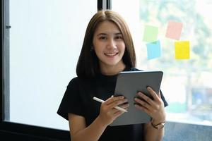 een vrouwelijke bedrijfsmedewerker gebruikt een tablet en een notitieblok om de bedrijfsbudgetten te analyseren foto