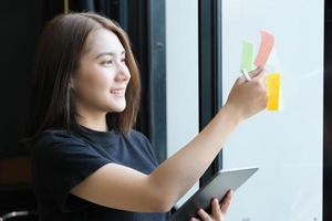 een vrouwelijke bedrijfsmedewerker die kladblok en tablet gebruikt om bedrijfsbudgetten te analyseren foto
