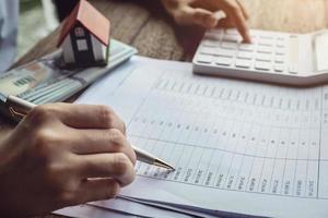 klanten gebruiken pennen en rekenmachines om leningen voor de aankoop van een huis te berekenen foto