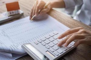 klant gebruikt pen en rekenmachine foto