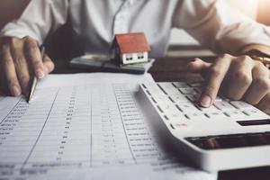 klant gebruikt pen en rekenmachine om de lening voor de aankoop van een huis te berekenen foto