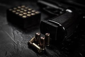 pistool met patronen op zwarte betonnen tafel foto