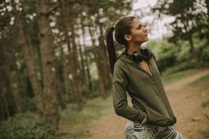 jonge mooie vrouwelijke atleet luisteren naar muziek en een pauze nemen na het joggen in een bos foto