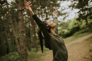 jonge vrouw met koptelefoon preading haar armen in het bos omdat ze graag buiten traint foto