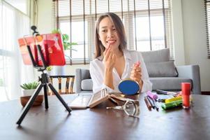 Aziatische blogger influencer vrouw die smartphone gebruikt using foto