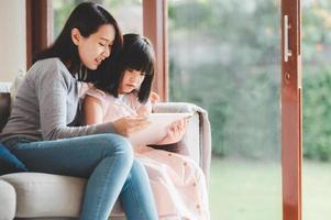 gelukkige Aziatische familie die digitale tablet gebruikt om thuis samen te studeren foto