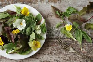 mix van salade met bloemen op een wit bord foto