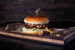 cheeseburger op een houten dienblad in een restaurant, op een donkere achtergrond foto