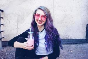 gelukkige mooie tiener met roze zonnebril drinkt en geniet van een roze drankje zittend op stedelijke grond foto