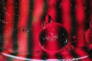 een mooie en kleurrijke levendige macro van oliebellen op water met een roze en zwart contrast als streeptextuur en achtergrondpatroon foto