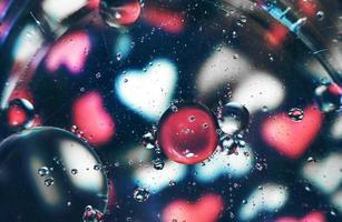 een mooie en levendige macro van oliebellen op water met een vervaging van wit en roze hartenpatroon op zwarte achtergrond foto