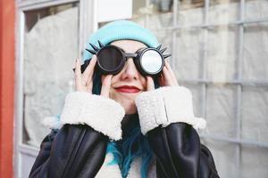 portret van een punk of gothic jonge vrouw glimlacht met blauw gekleurd haar en het dragen van een zwarte steampunk bril en blauwe wollen muts in een stedelijke buitenstraat foto