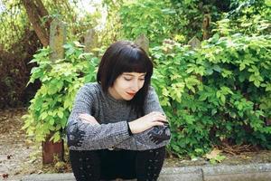 mooie kaukasische brunette vrouw zittend op de grond in een park, gekleed in punk of gotische kleding en omringd door groene bladeren foto