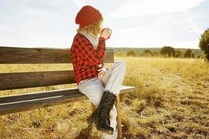 een jonge vrouw van achteren in een rood geruit hemd met een wollen muts en sjaal die een kopje thee of koffie neemt terwijl ze zonnebaadt zittend op een houten bank in een geel veld met achtergrondverlichting van de herfstzon foto