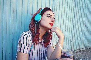 mooie roodharige vrouw die naar muziek luistert foto