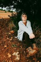 vrouw van middelbare leeftijd alleen in de natuur in een koude herfstdag foto