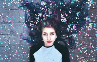 coole jonge vrouw omringd door confetti foto