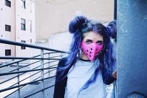 jonge punkvrouw met een roze masker foto