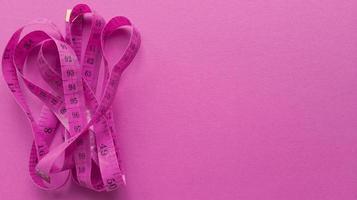 roze centimeter op roze achtergrond. eenvoudig plat leggen met pasteltextuur. fitness-concept. Stock foto. foto