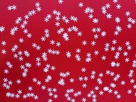 verspreide witte sneeuwvlokken op rode achtergrond. eenvoudig feestelijk plat leggen. Stock foto. foto