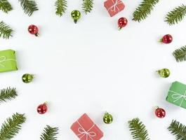 kerst plat lag met kopieerruimte in het midden. vakantie ansichtkaart met sparren takken, groene en rode kerstballen, geschenkdozen op een witte achtergrond. foto
