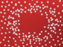 verspreide witte sneeuwvlokken op rode achtergrond. eenvoudig plat leggen met kopieerruimte. Stock foto. foto
