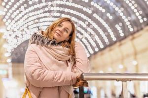 een mooie jonge vrouw staat in een winkelcentrum met een bokeh van veel gloeilampen op de achtergrond. foto