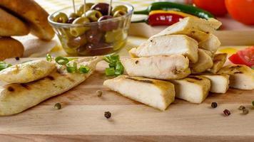 gegrild kippenvlees op houten plaat met groenten en olijven op de achtergrond. foto