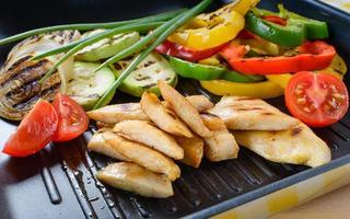 gegrild kippenvlees op de grill met groenten op de achtergrond. foto