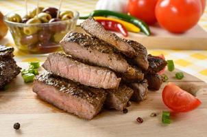 gegrild rundvlees op houten plaat met groenten en olijven op de achtergrond. foto
