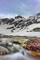 waterloop die naar beneden komt van de berg waar de sneeuw in de lente wordt gesmolten foto