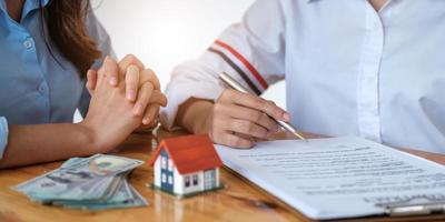ervaren makelaar die het huismodel aan de klant laat zien en klaar is om een contract te ondertekenen foto