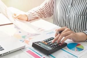 zakenvrouw met behulp van een rekenmachine en het schrijven van notities. belastingen, besparingen, financiën en economie concept foto
